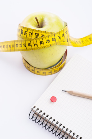 metering: Fresh and green organic apple with metering tape and notebook over white background Stock Photo