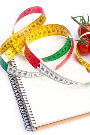 metering: Notebook with metering tape and tomatoes over white background Stock Photo
