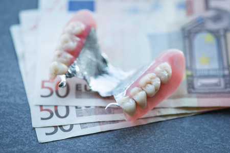 artificial teeth: Artificial replacement teeth with money on a dark surface Stock Photo