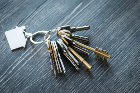 tresspass: Bunch of keys with house shaped key ring on a rustic wooden table Stock Photo