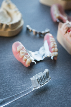 artificial teeth: Artificial replacement teeth with tooth brush on a dark surface Stock Photo