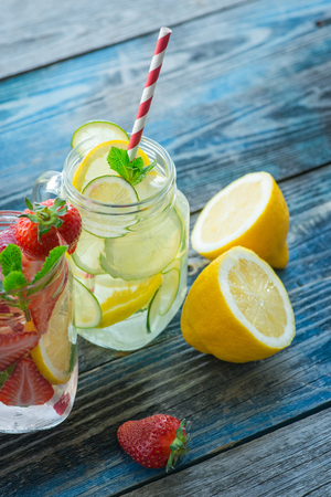 jugs: Jugs with lemon, lime and strawberry infused water on a rustic wooden table