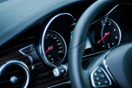 rev: Luxury car interior details. Speedometer and steering wheel