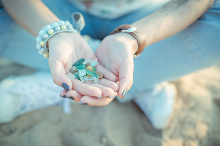 washed out: Sea glass pieces in the hands of a young woman Stock Photo