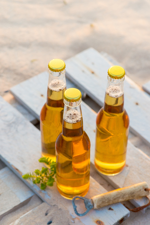 rusty nail: Three beer bottles standing on the rustic wooden board
