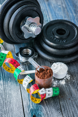 muscle gain: Classic dumbbell with protein powder on wooden table Stock Photo
