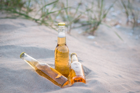 Three cold beer bottles in the warm sand