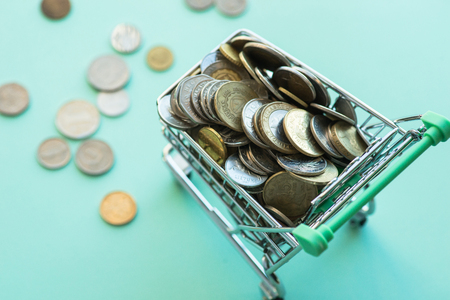 Shopping cart full of coins over the light green background Stock Photo