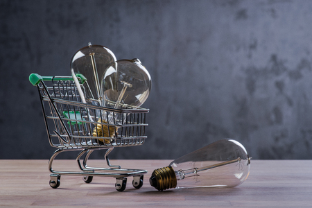 Shopping cart with vintage bulbs on wooden table Stock Photo