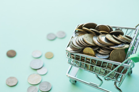 pushcart: Shopping cart full of coins over the light green background Stock Photo