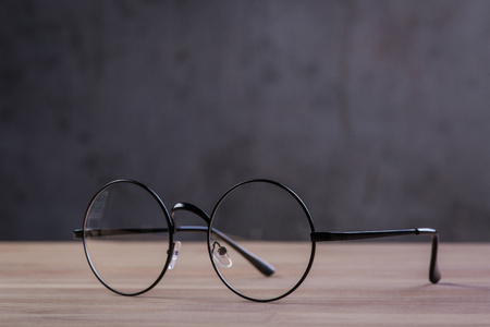 round: Vintage reading glasses on the wooden table Stock Photo