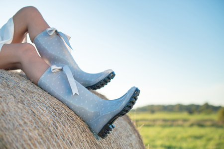 Girl in rain boots sitting on the haystack in the field Stock Photo