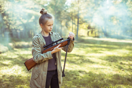 sniper training: Young girl shooting from the air rifle in the forest