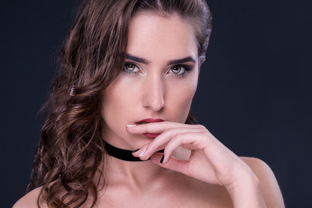 smoky black: Beauty. Portrait of a young woman with choker over dark background Stock Photo