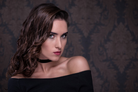 Beauty. Portrait of a young woman with choker over dark background Stock Photo
