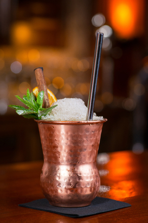 Cocktail. Mint Julep drink with orange in copper glass and steel straw