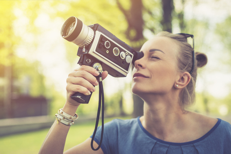 filmmaker: Summer. Young beautiful woman with vintage camera in the park Stock Photo
