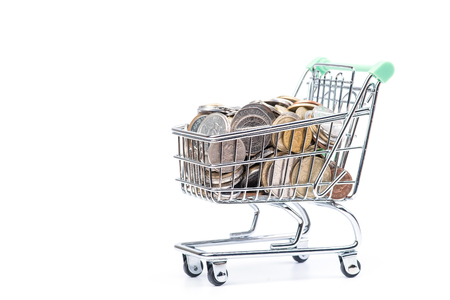 Shopping cart loaded full with coins. Isolated on white Stock Photo