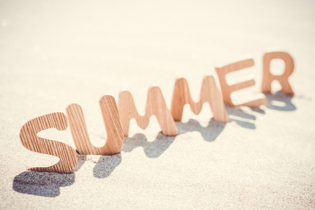 Summer. Wooden letters on the sand under the sun