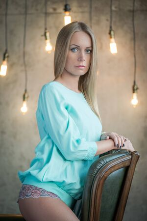 boudoir: Beauty portrait. Portrait of a beautiful woman on the armchair by the wall with vintage bulbs Stock Photo