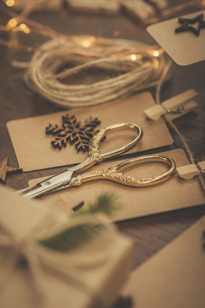 Christmas. Gifts. Vintage style scissors with gift boxes on a rustic wooden table