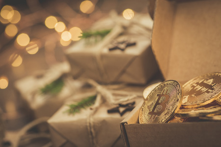 Christmas. Gifts. Bitcoins in a vintage style gift box on a rustic wooden table Фото со стока