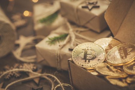 Christmas. Gifts. Bitcoins in a vintage style gift box on a rustic wooden table Banco de Imagens