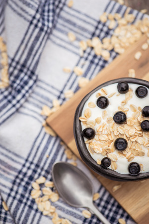 Yogurt. Flatlay. Stone bowl with fresh greek yogurt and berries