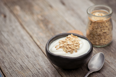 Yogurt. Stone bowl with fresh greek yogurt on wooden table Standard-Bild