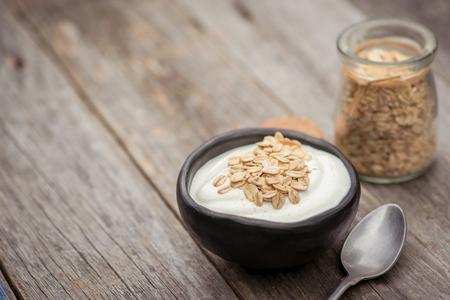 Yogurt. Stone bowl with fresh greek yogurt on wooden table Banco de Imagens