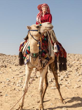 Egypt, Giza, Woman on camel in desert