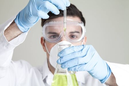 adding: Scientist adding green liquid to conical flask