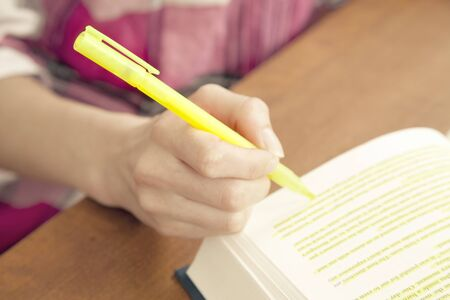 highlighter pen: Woman highlighting passage in book, close up