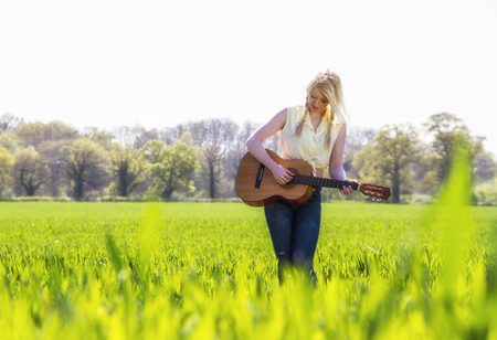 plucking: Female country singer in grass field LANG_EVOIMAGES