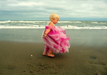Blonde toddler fighting windy day on beach in pink dress