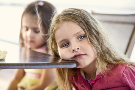 Two girls (4-5) at table, one resting cheek on table edge LANG_EVOIMAGES