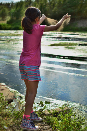 an only child: Girl (8-9) throwing sand by lake