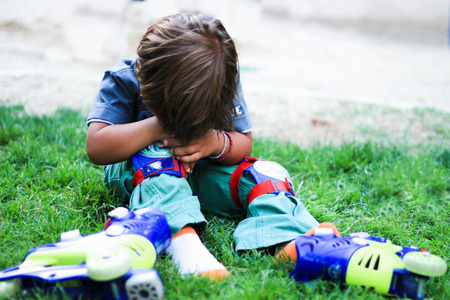 Spain, Madrid, Little boy with roller skates sitting on grass and crying
