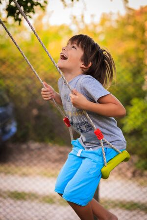 chainlink fence: Boy laughing and swinging on a swing