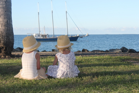 Australia, Queensland, Port Douglas, Rear view of two girls (4-5) sitting on grass looking at boat on sea LANG_EVOIMAGES