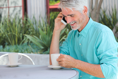 Businessman having cup of coffee while talking on phone