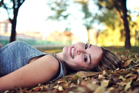 Portrait of smiling young woman lying on leaves outdoors LANG_EVOIMAGES