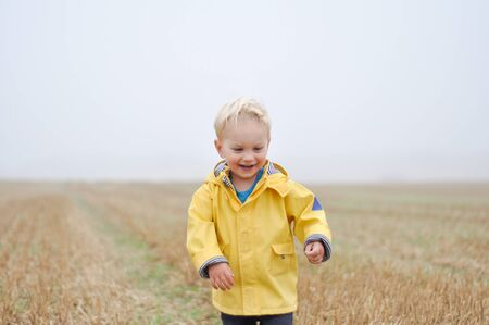 Front view of boy in field in rainwear LANG_EVOIMAGES