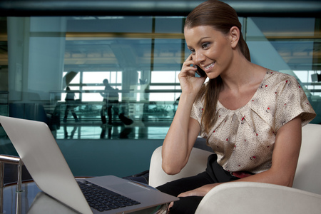 Businesswoman sitting in airport lounge with phone and laptop LANG_EVOIMAGES