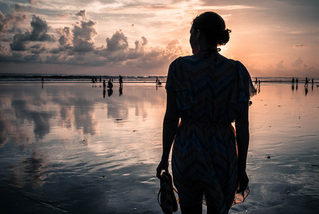 Indonesia, Bali, Legian, Silhouette of woman on beach at sunset LANG_EVOIMAGES