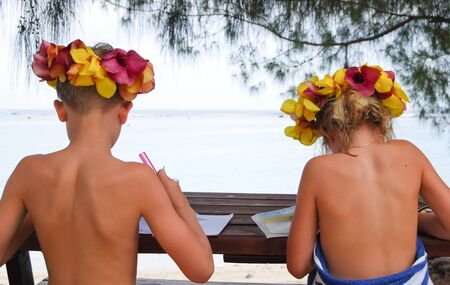 Cook Islands, Rarotonga, Children studying on beach LANG_EVOIMAGES