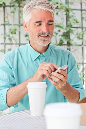 Businessman making call in sidewalk cafe