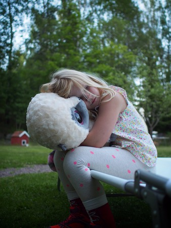 Sweden, Girl (6-7) hugging teddy bear in backyard