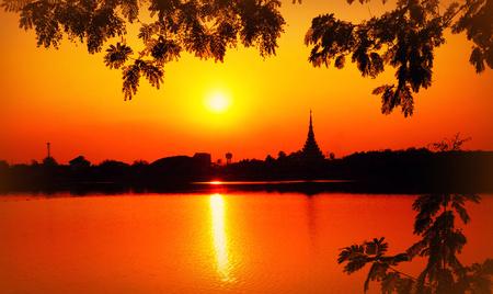 Thailand, Khon Kaen Province, Khon Kaen, Ban Ganyarat, Rob Bueng Road, Bueng Kaen Nakhon, Sunset and temples over Bueng Kaen Nakhon Lake