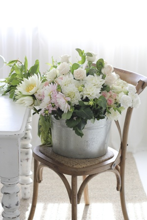 dining table and chairs: Bucket of flowers on chair